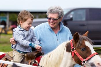 Boy Rides A Pony At A Fair